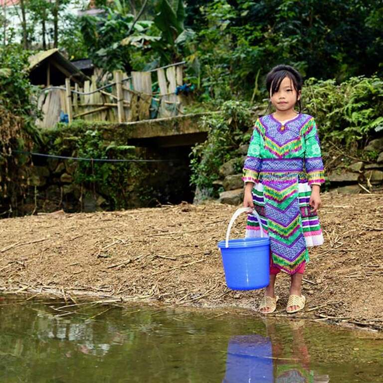 Little Tra, 8 years old, wears a colorful outfit stands on the bank of a river near her home, holding a blue plastic bucket.
