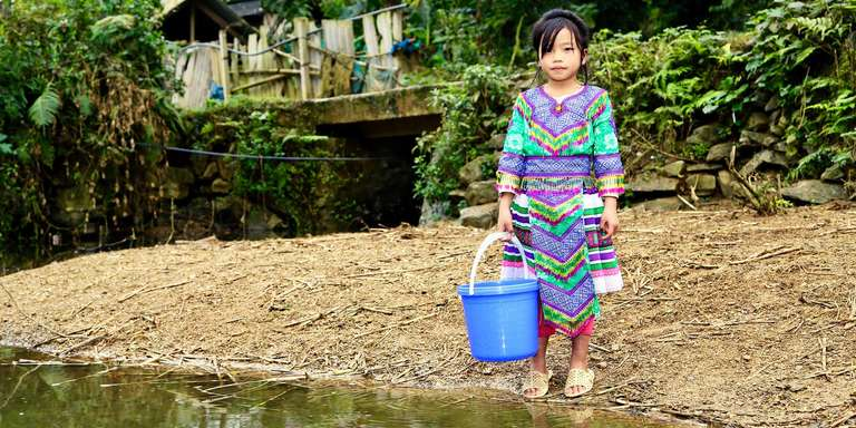 An eight-year-old girl stands by a river holding a blue bucket used to collect water. Before her community in Vietnam received a water well from Save the Children, she had to rely on the river, which is not clean, for all her water needs. Photo credit: Matthew Morrison, Save the Children, Jan 2018.