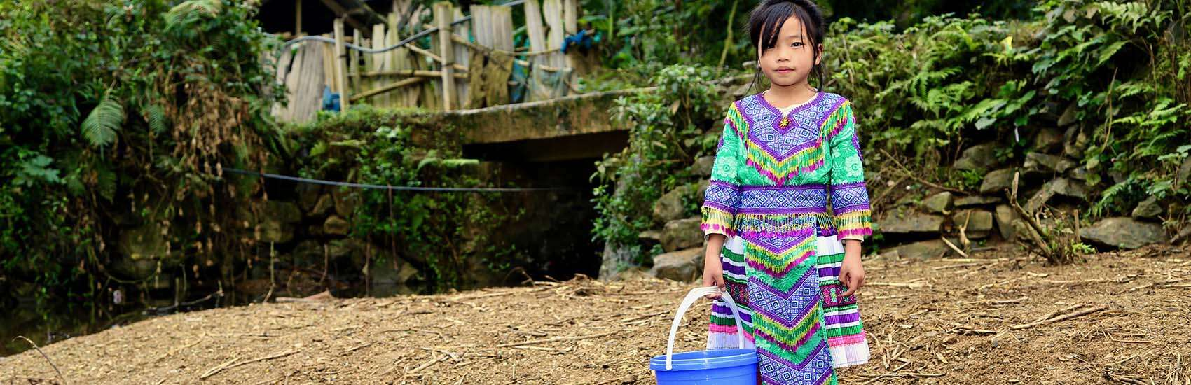 A young girl holds a blue bucket while standing next to a small river in Vietnam.