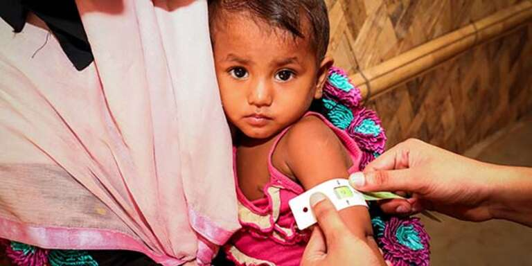 Baby Laila*, 22 months old, is measured with a MUAC band in a Save the Children Health Assessment Centre in Leda Camp, Cox's Bazar, Bangladesh.