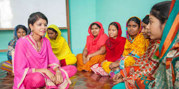 A group of women seated on the floor sit cross-legged and listen intently to one another during a discussion of vocational training of working teenagers in Bangladesh. Save the Children supports programs around the world aimed at changing dangerous working conditions for children. Photo credit: Save the Children, March 2017.