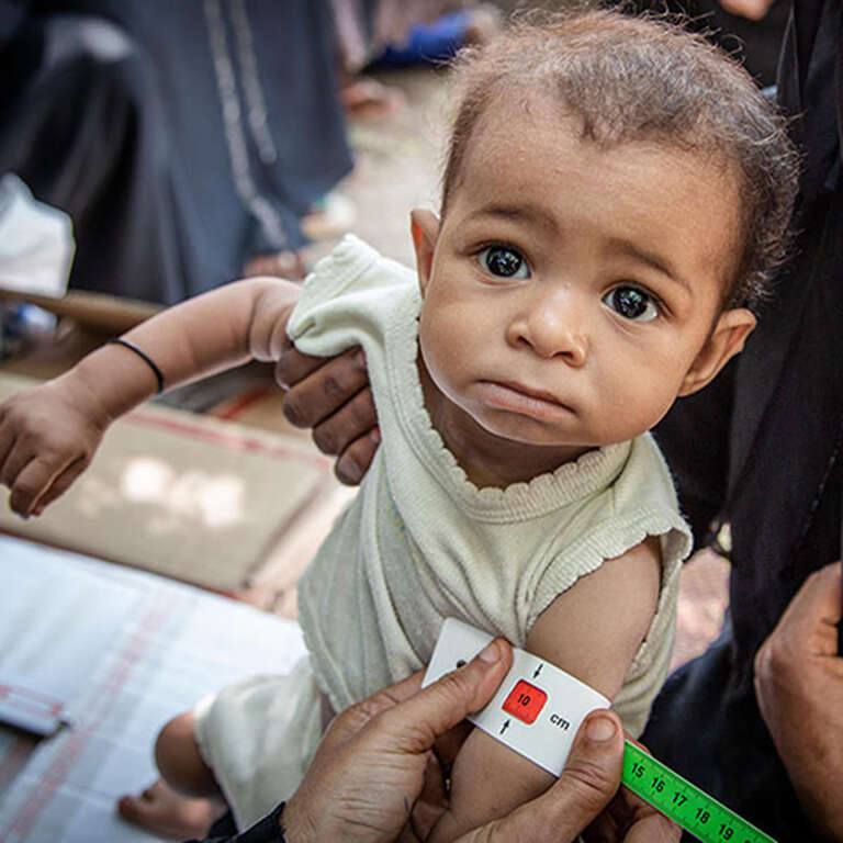 A baby in Yemen receives care from a medial worker.