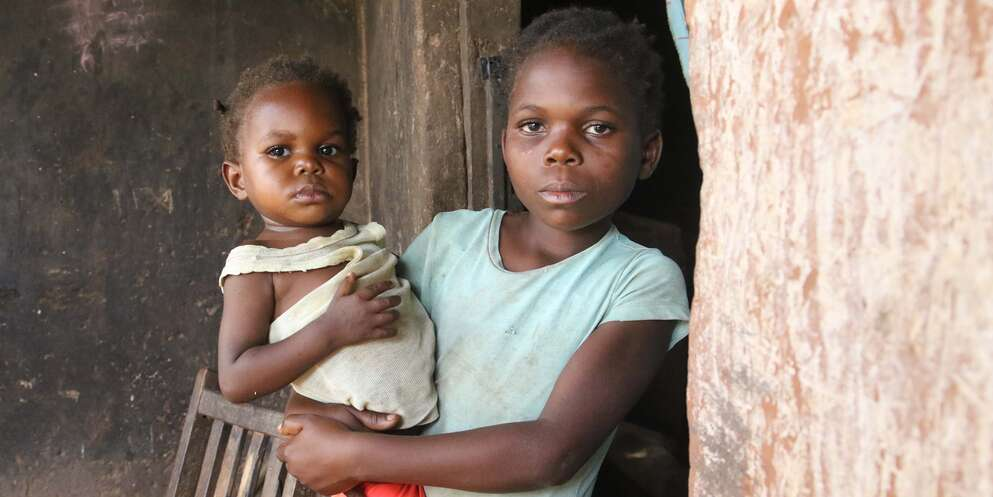 A 9-year old girl holds her one-year old baby sister on her hip outside their cement home in the Democratic Republic of Congo.