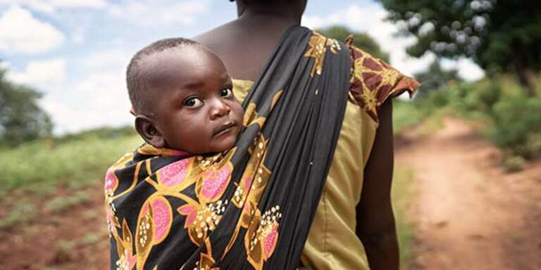Memory with her son Joseph in a sling on her back, in Malawi.