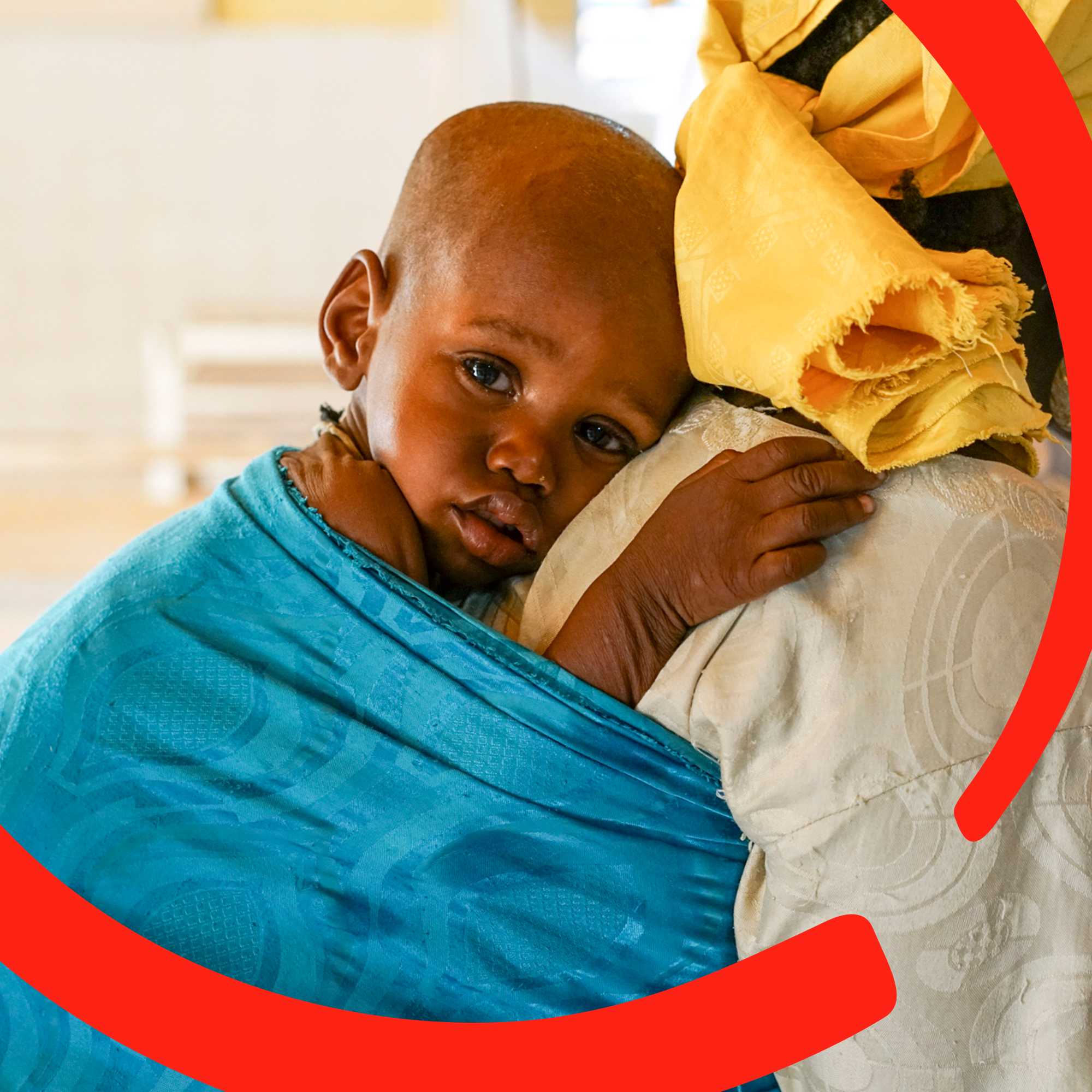 A 19-month old baby boy clings to his mother, who carries him on her back in a blue wrap. The boy has been treated for malnutrition at a stabilization center funded by Save the Children in Niger. Photo credit: Talitha Brauer / Save the Children, July 2016.