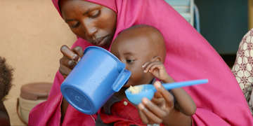 A woman feeds her child from a blue cup.