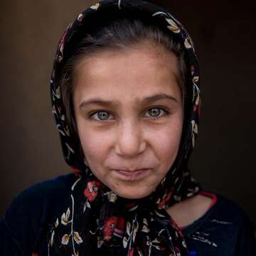 An eight-year old girl who lives in Kabul province, Afghanistan stands alone and looks directly at the camera.