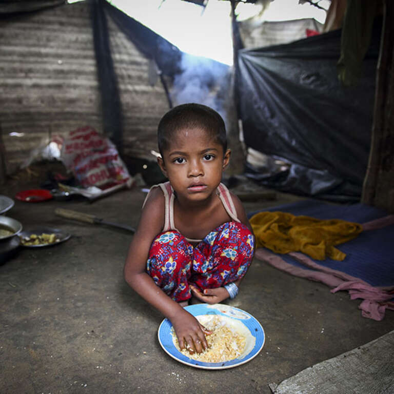 A 5-year-old squats on the floor in a makeshift camp in Cox's Bazar district, Bangladesh, where she and her family are living. The family fled Myanmar when their village was attacked. Photo credit: GMB Akash / Panos Pictures / Save the Children / Save the Children, Oct 2017.