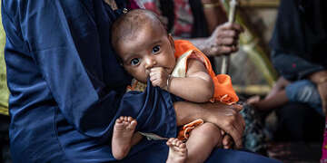 A Rohingya mother sits holding her baby as they wait to be seen by medical staff at Save the Children's primary health care centre, in a camp for refugees in Cox's Bazar, Bangladesh.