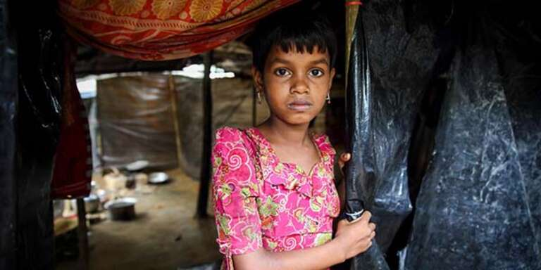 A 9-old girl who fled Myanmar with her family stands alone in a makeshift camp in a Cox's Bazar refugee camp