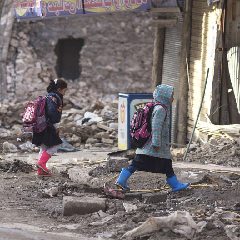 Children walk home from school in Mosul, Iraq in January 2019. The city of Mosul was severely damaged in fighting. Much of the housing was reduced to rubble.  Credit: Sam Tarling / Save the Children