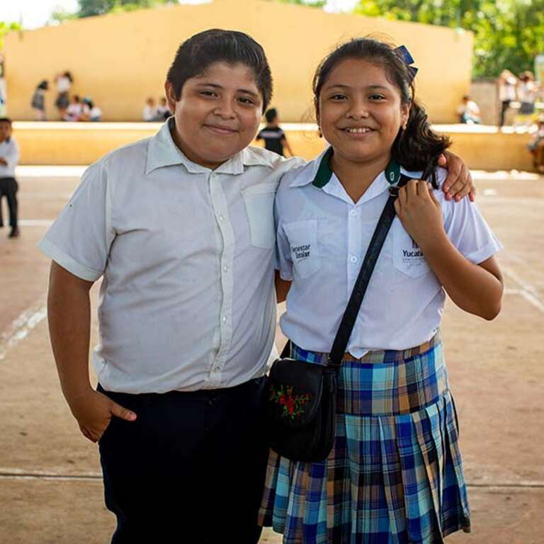 Two school children stand next to one another outside a school in Mexico.
