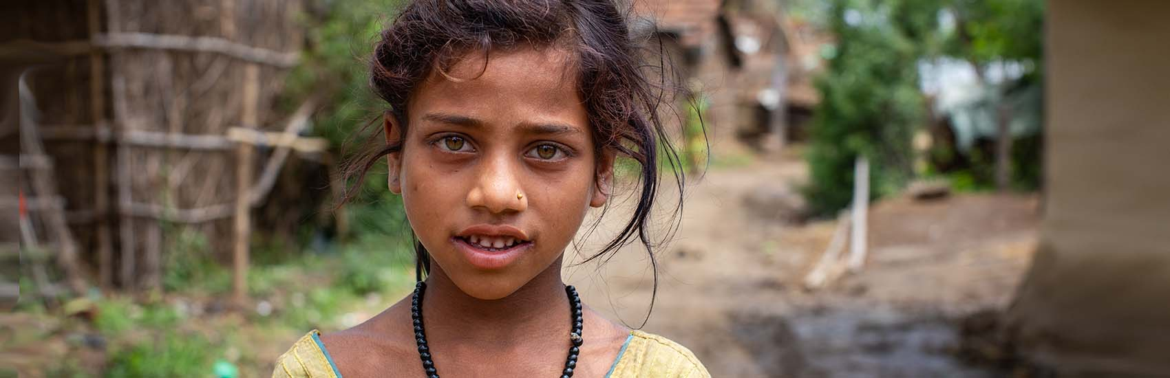 An 8-year-old girls stands outside of her home in Nepal by herself.