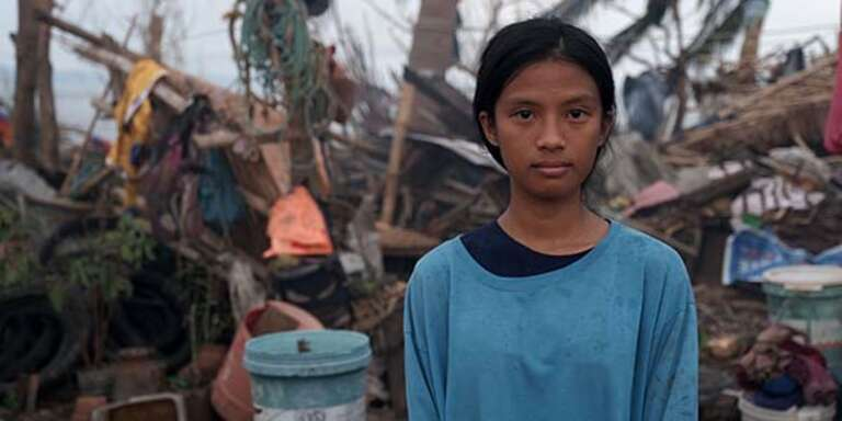 A 16-year old girl stands in front of a damaged structure destroyed in Typhoon Goni in the Phillipines.