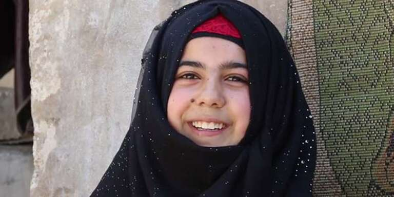 A teenage girl wears a black headscarf and smiles at the camera.