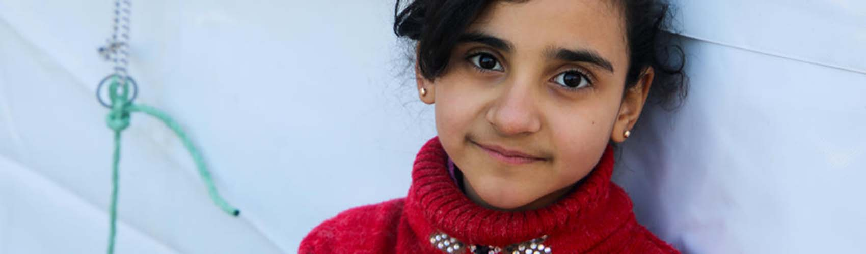 A young girl wearing a red sweater leans against a wall in Syria.