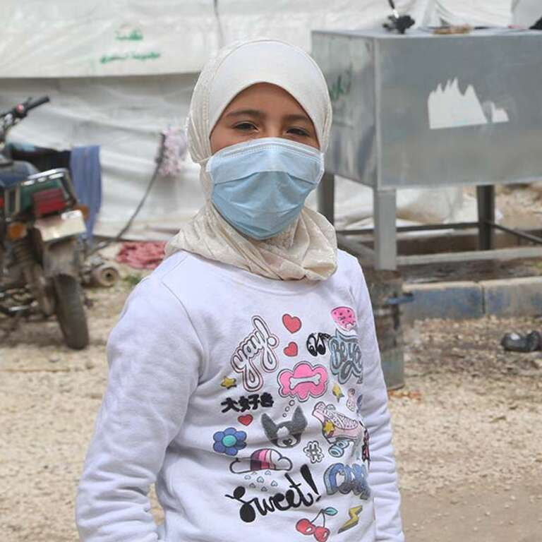 A 10-year old girl wears a protective face covering in North West Syria.