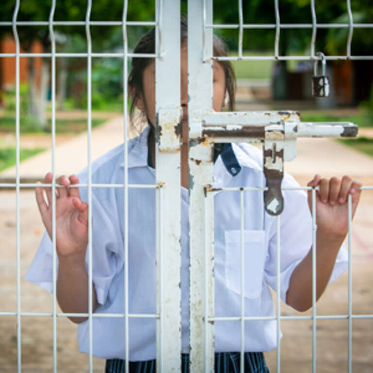 A girl in a white shirt stands behind a white iron gate with her face covered.