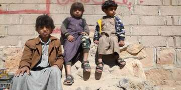 Abed*, 11, sits with his siblings atop a pile of rubble in Yemen.