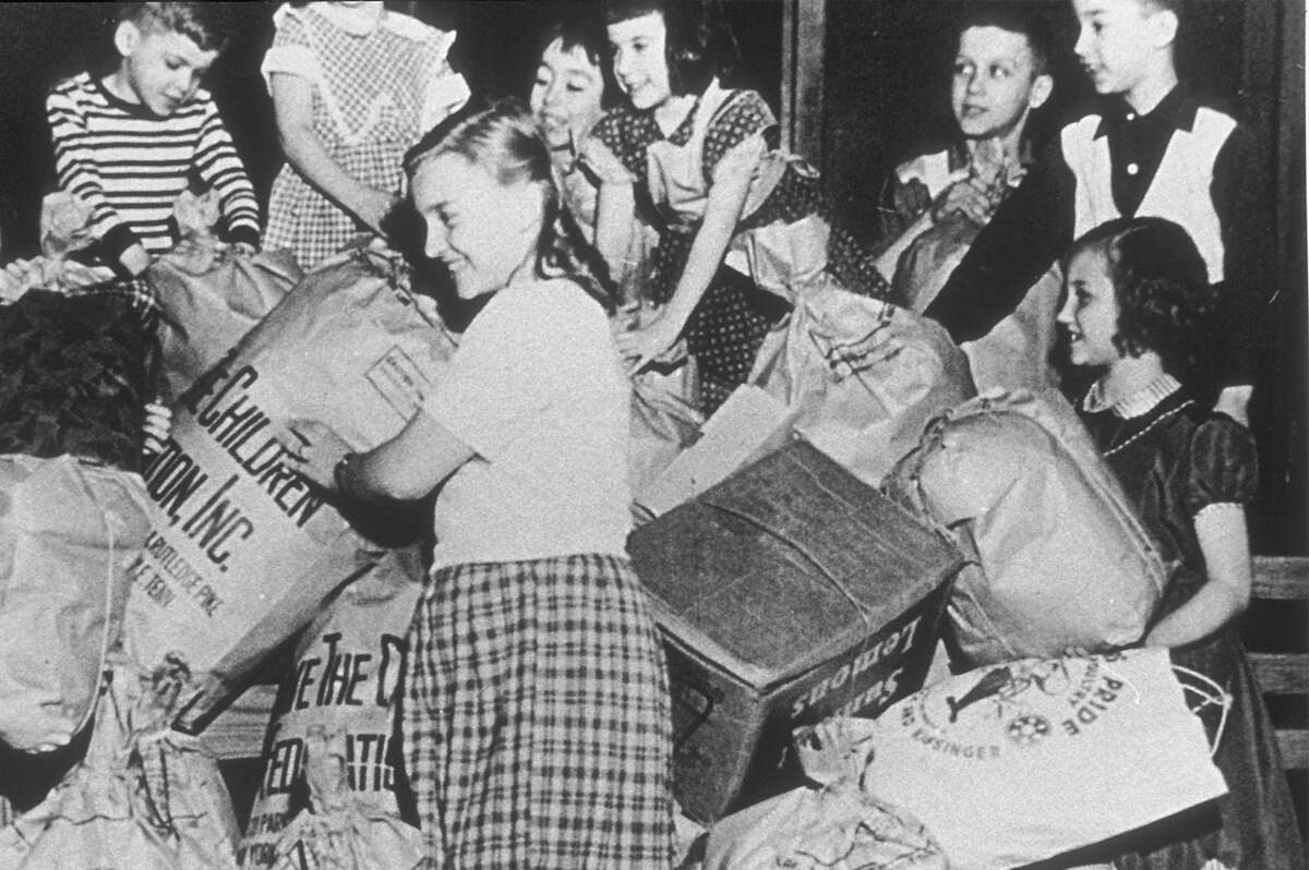 "A black and white photo from 1941 depicting volunteers distributing donated clothing to needy children in the United States and war-affected Europe. Save the Children's first annual ""Bundle Days"" campaign in Knoxville, Tennessee is part of our 100-year history of doing whatever it takes for children in need. Photo credit: Save the Children"