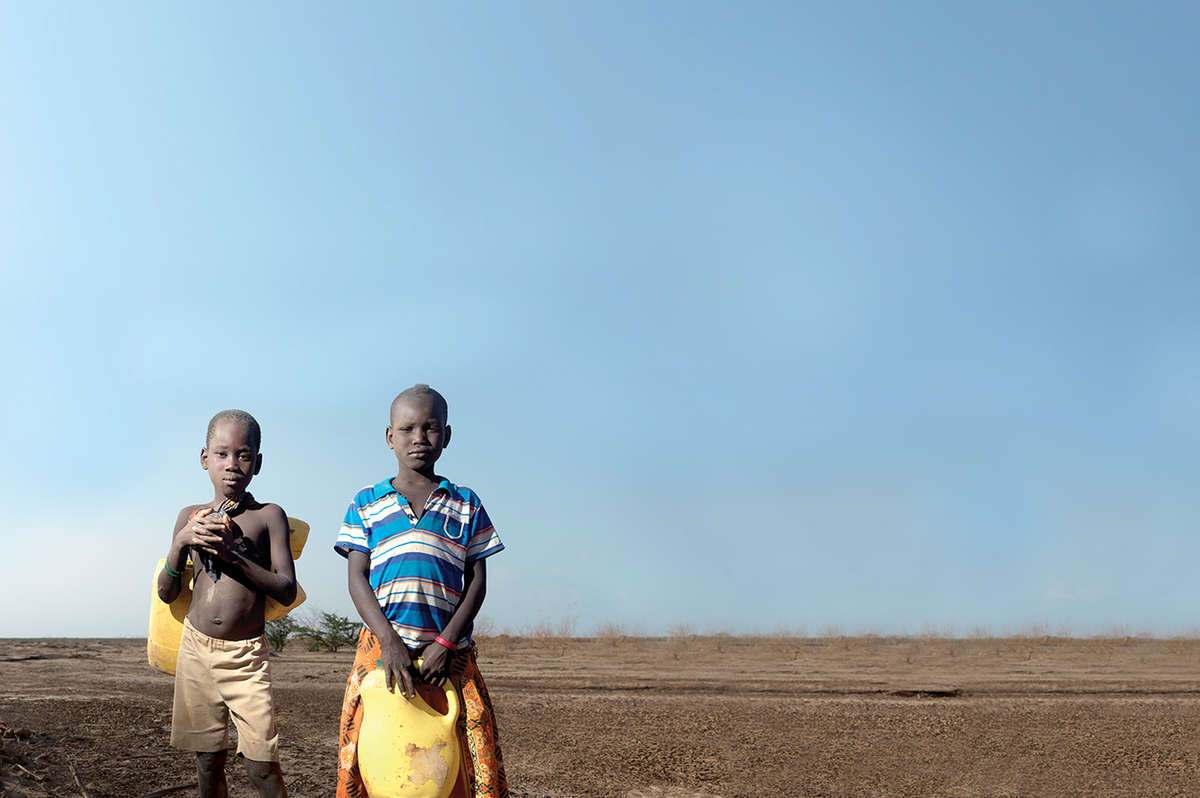 Two boys James, 6 and Heshima, 8 hold large yellow water jugs. They stand in a dusty, dried-up river bed in Turkana County, Kenya. Photo credit: Peter Caton/Save the Children, July 2017.