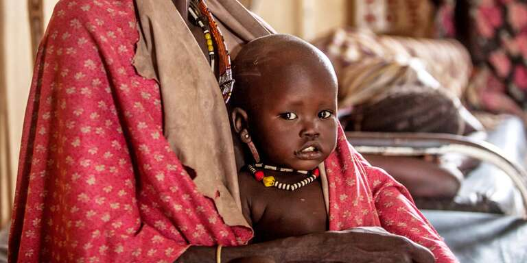 One year-old Hakaroom sits with his mother Lokuru at a Save the Children-supported health center in Kapoeta, South Sudan, after being treated for severe pneumonia. Photo credit: Martin Kharumwa / Save the Children, Oct 2017.