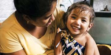 A healthy Filipino girl sits on her mother's lap and smiles for the camera. Save the Children provided Jasmine with high-energy therapeutic food after she was diagnosed with malnutrition. Photo credit: Carlo Gabuco / Save the Children, July 2017.