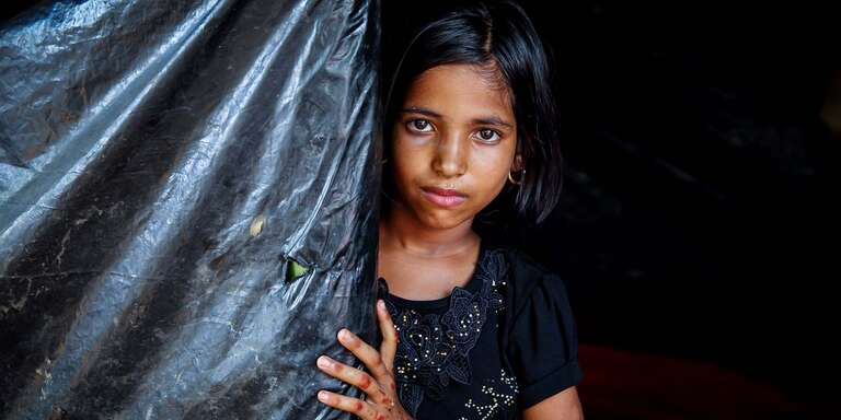 An 8-year-old girl looks out from behind a dark tarp. The girl and her family fled Myanmar when their village was attacked. They now live in a makeshift camp in Cox's Bazar district, Bangladesh. Photo credit: GMB Akash / Panos Pictures / Save the Children, Oct 2017.