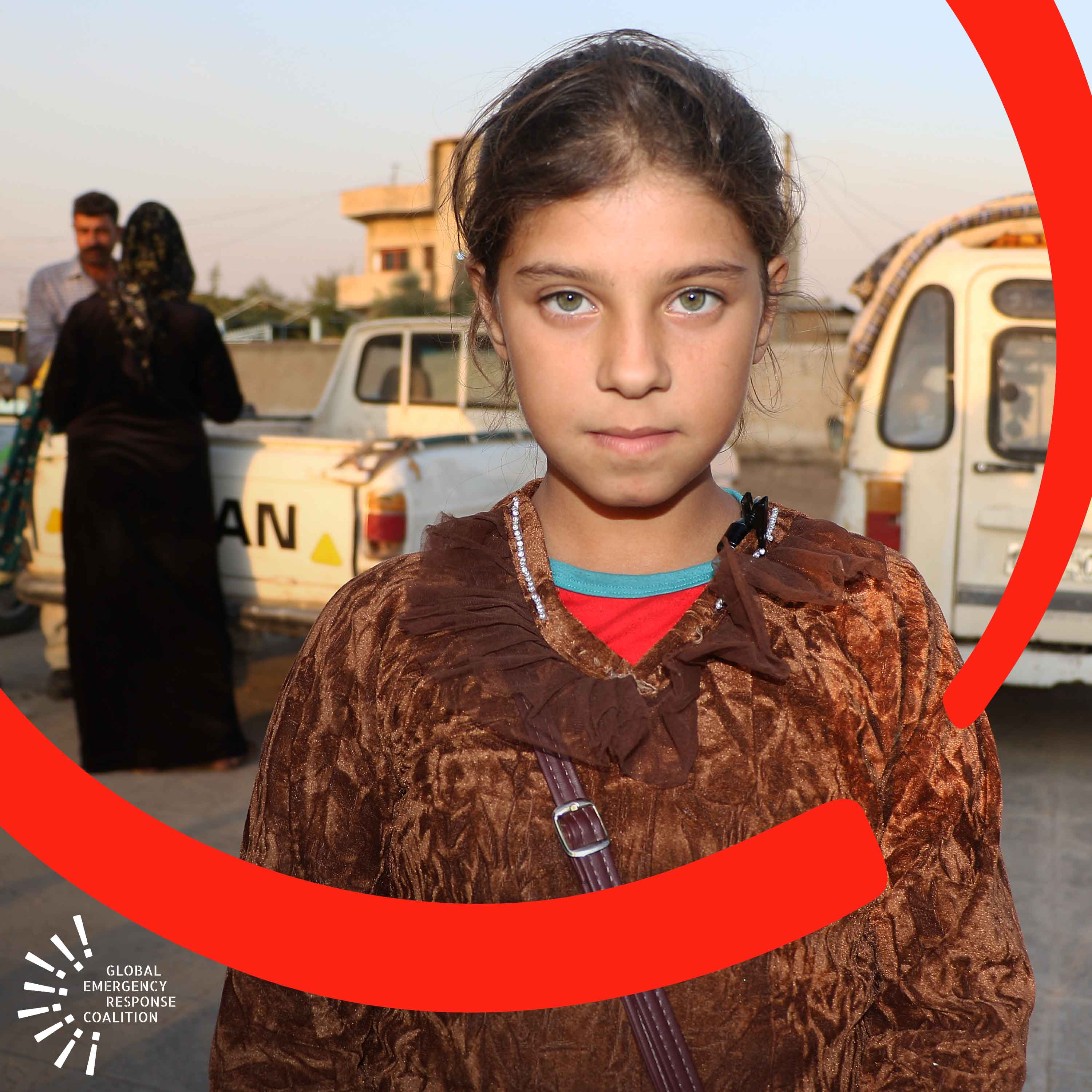 An 11-year old girl who has been displaced with her family in Syria stands in front of a school bus.