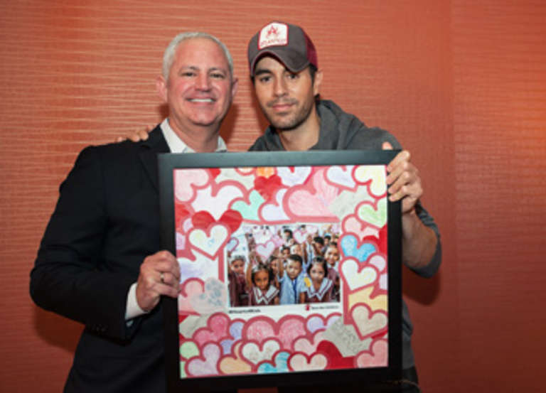Save the Children's Carlos Carrazana surprises Enrique Iglesias with valentines from kids in Save the Children's Filipino programs.