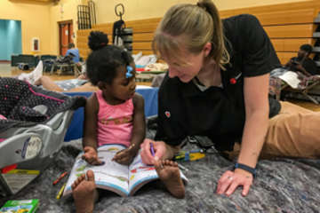 Sarah Thompson, Director of Preparedness, Save the Children U.S. Programs colors with 2-year-old Eliyah