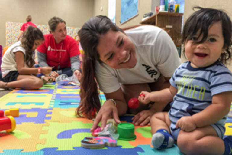 Mario*, 9-months-old, plays with his mother Emily in Save the Children's child-friendly space