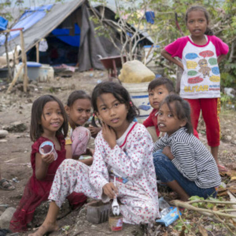 A group of seven young children are gathered in a space littered with branches, blankets and trash. When their homes were destroyed in the 2018 Indonesia earthquake and tsunami, theylived in a temporary shelter and survived on supplies provided by Save the Children and other aid organizations. Photo credit: Ardiles Rante / Save the Children, Oct 2018.