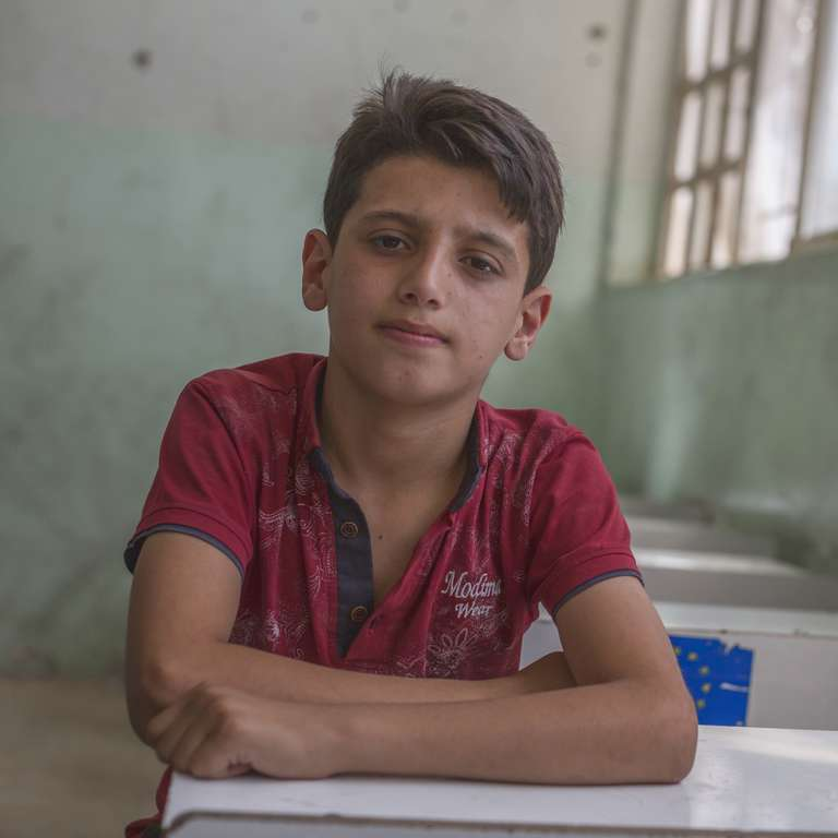 A 12-year-old student sits in his school in West Mosul, which was damaged extensively during the fighting between Iraqi forces and ISIS. Photo credit: Sam Tarling/Save the Children 2018.