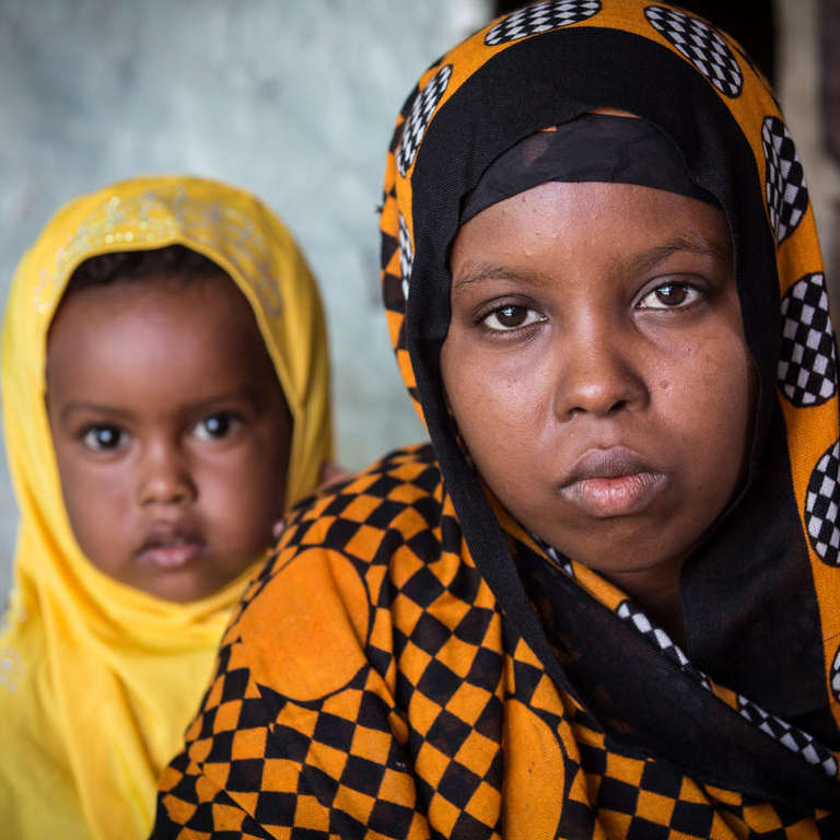 Aisha*, 15, former child bride, with her two year-old daughter Rayan*.  Photo credit: Colin Crowley / Save the Children