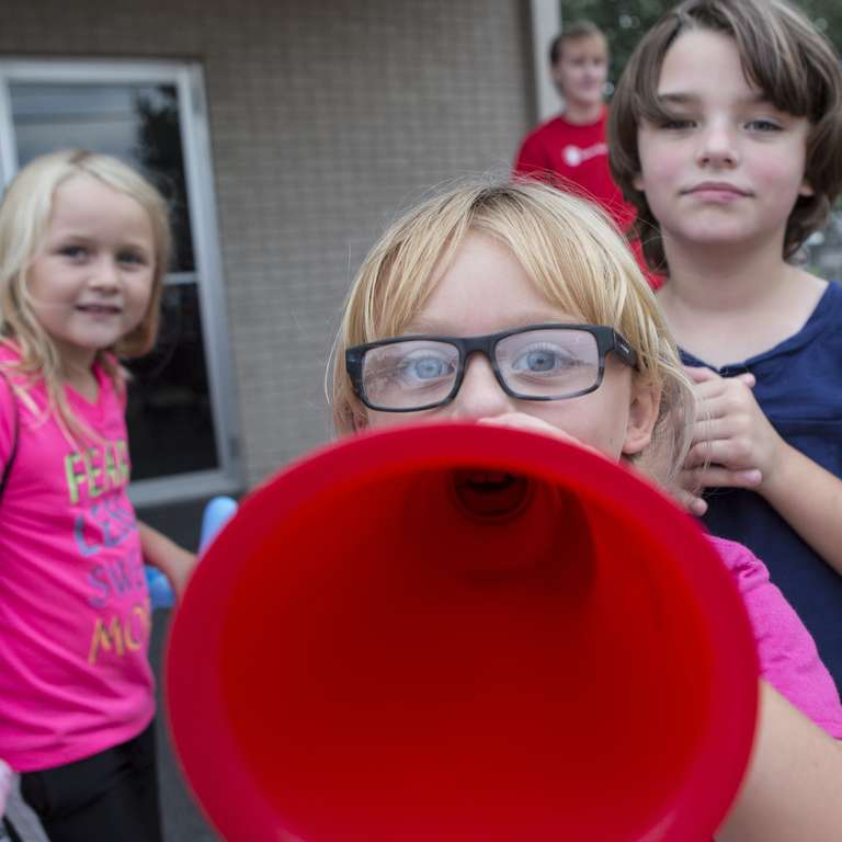 Children play outdoors with a megaphone at a celebration for the 20th anniversary of Agapeland Learning Center, in Moore, OK. In 2013, Save the Children helped reopen the center after a tornado ripped the roof off the building while children and teachers sheltered inside. Photo credit: Brett Deering/Save the Children, September 2016.