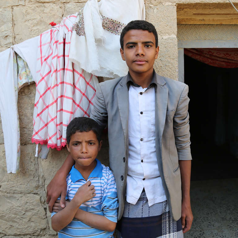 Hamza*, 16, with his brother Hani*, 12, outside their home in Amran, Yemen. Hamza*, helps provide for his mother and five siblings. He was injured on the first day of airstrikes in Sana'a when a shell injured him and broke his leg. Photo Credit: Mohammed Awadh/Save the Children.