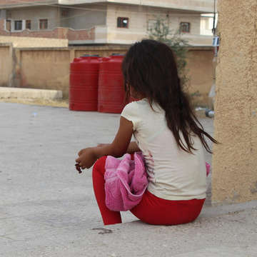 A young girl sits outside her shelter. More than 13,000 people – including approximately 5,200 children – are currently seeking refuge in more than 30 collective shelters. These shelters are schools and unfinished buildings without electricity, as well as open fields across Al Hasakeh, Tal Tamer and Al Raqqa. Photo credit: Save the Children 2019.