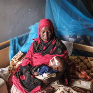 Alafi, 35, holds her 18-month-old son at a hospital in Kabridahar, Ethiopia in June 2019. He was diagnosed with Severe Acute Malnutrition and anemia and transferred to the special children's ward, which is supported by Save the Children. Credit: Eduardo Soteras Jalil/Save the Children.