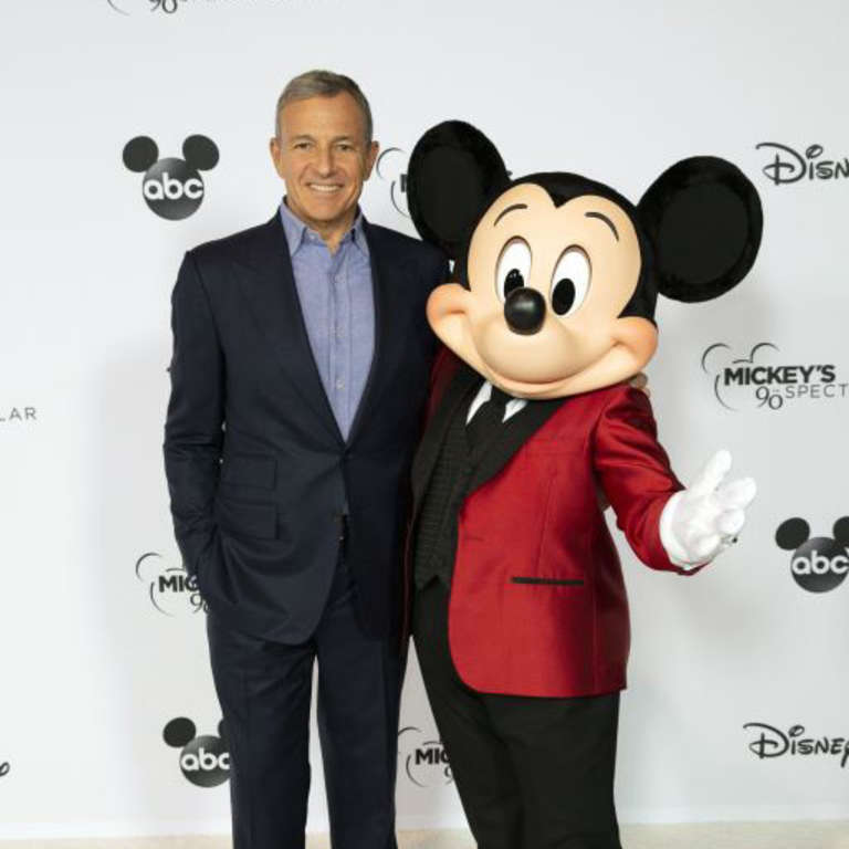 Robert Iger and Mickey Mouse together smiling.