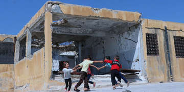 Children that may not be going to school this year, play outside their school in Idlib Syria.