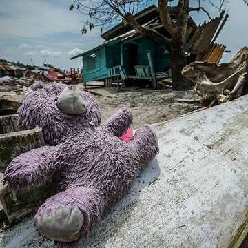A teddy bear lays strewn across wreckage on the beach after the Sulawesi Indonesia earthquake and tsunami. In the background, a family's home is in shambles, torn apart by the tsunami's crushing wall of water. Photo credit: Thomas Gustafian / Save the Children