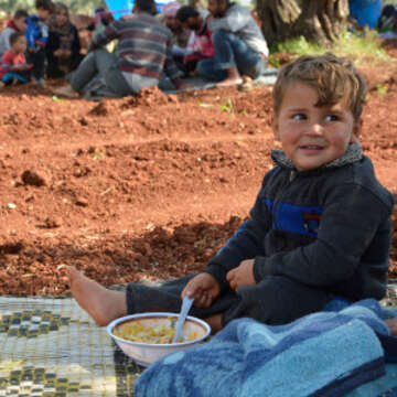 A child eats at a temporary camp for those who have fled fighting in Idlib, Syria, May 2019. Over 180,000 people have escaped an upsurge in violence in Idlib over the last few weeks. Credit: Save the Children.