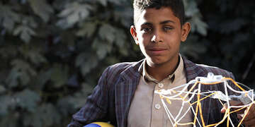 Eyad* made the basketball hoop he is holding himself with rope and wire