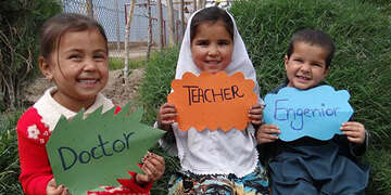 Three children in Afghanistan sit and hold hand-made signs for what they want to be when they grow up.