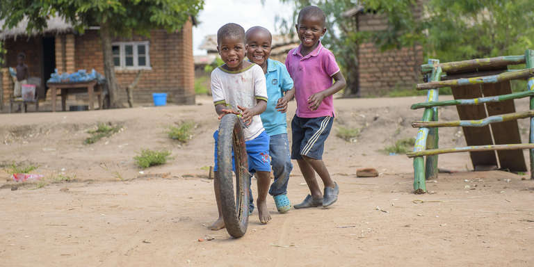 Three young boys smile joyfully while they play with a bicycle tire on a dusty playground in Malawi. Photo credit: Bennie Khanyizira / Save the Children, April 2018.