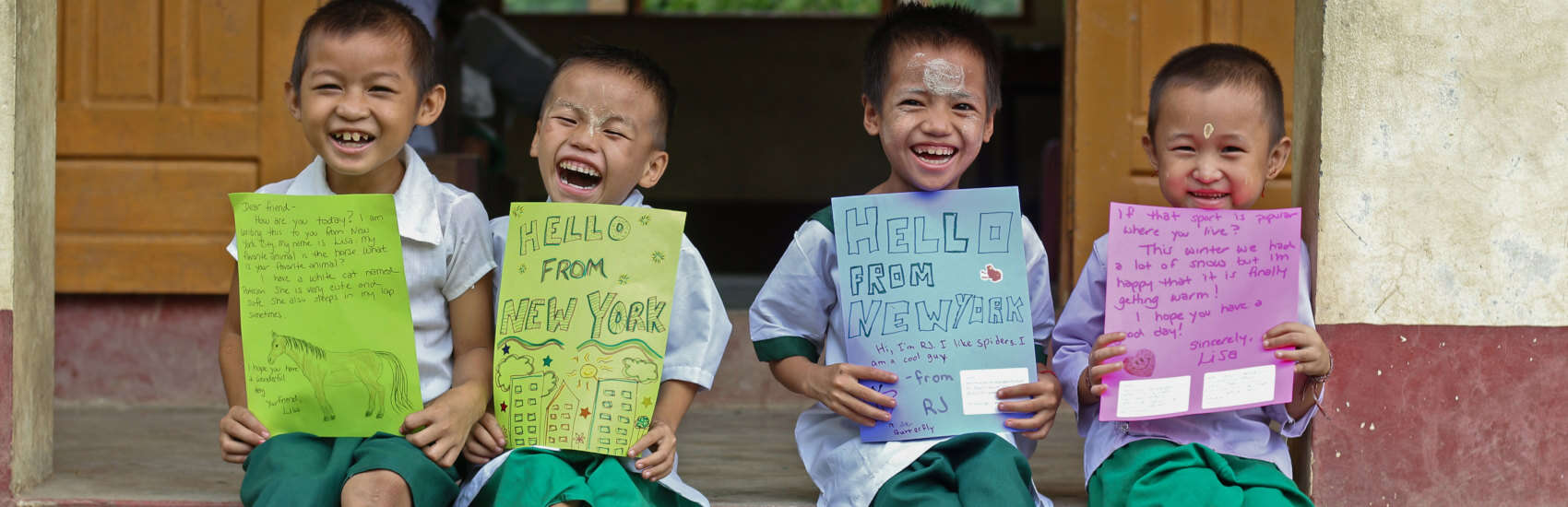 Four young boys in Myanmar hold up their Save the Children sponsor letters. Photo Credit: Save the Children Vietnam 2020.