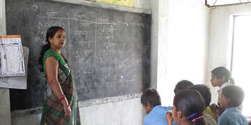 Teacher Mira stands in front of a class teaching in Nepal.