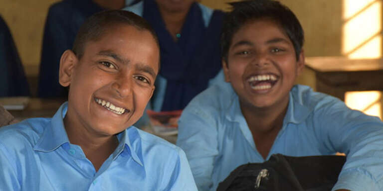Two boys wearing school uniforms sit together at a desk at a school in Nepal and laugh.