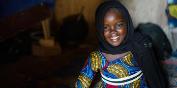 A girl stands in her home in Niger, where Save the Children has sponsorship programming